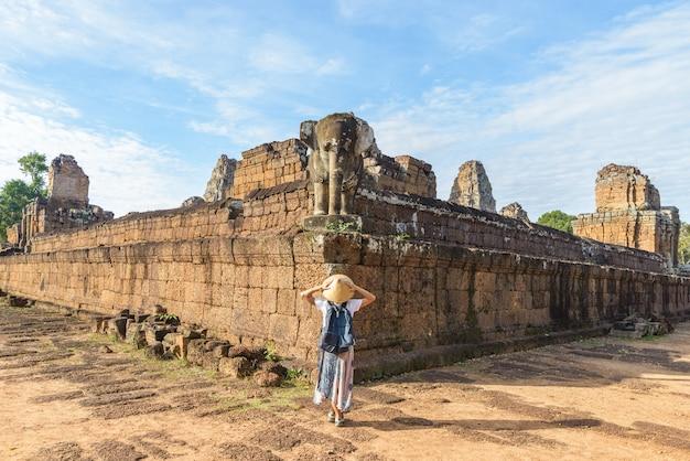 Un touriste visitant les ruines d'angkor wat au lever du soleil Photo Premium