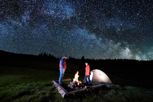 Touristes Couple Près De Feu De Camp Et Des Tentes Sous Le Ciel Nocturne Plein D'étoiles Et La Voie Lactée Photo Premium