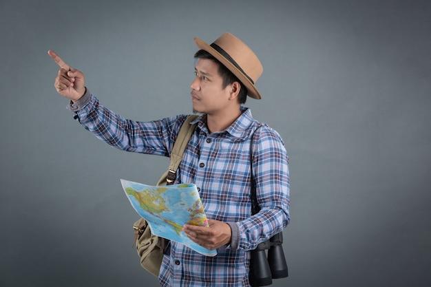 Touristes hommes portant des sacs à dos portant une carte de fond gris. Photo gratuit