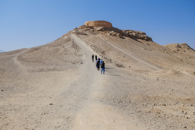 Touristes marchant dans les anciens bâtiments de dakhma zoroastrien. tour persane du silence. yazd, iran. Photo Premium
