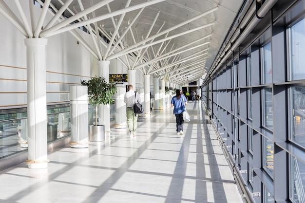 Les touristes marchent vers différentes portes en suivant l'étiquette de porte avec une flèche dans le terminal de Photo Premium