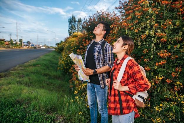 Les Touristes Masculins Et Féminins Portent Un Sac à Dos Debout Dans Un Jardin Fleuri. Et Regarde Vers Le Haut Photo gratuit
