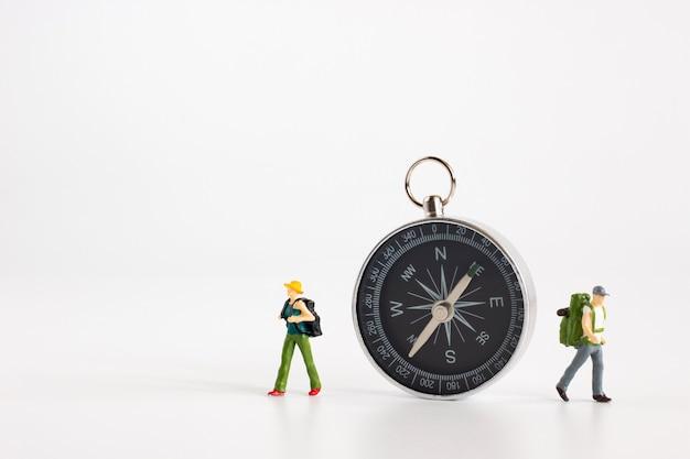Les touristes miniatures voyagent dans différentes directions avec une boussole sur fond blanc Photo Premium