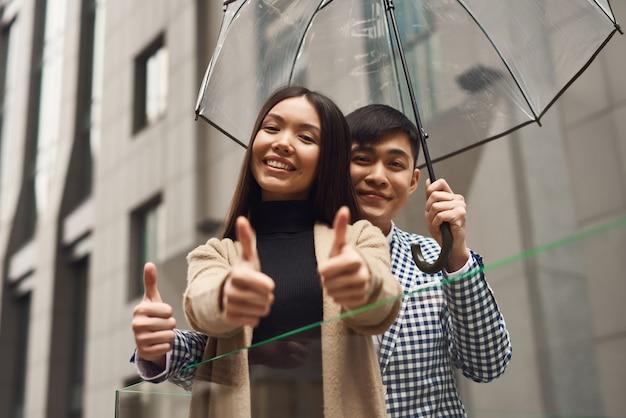 Les Touristes Avec Parapluie Garçon Et Fille Montrent Pouces. Photo Premium