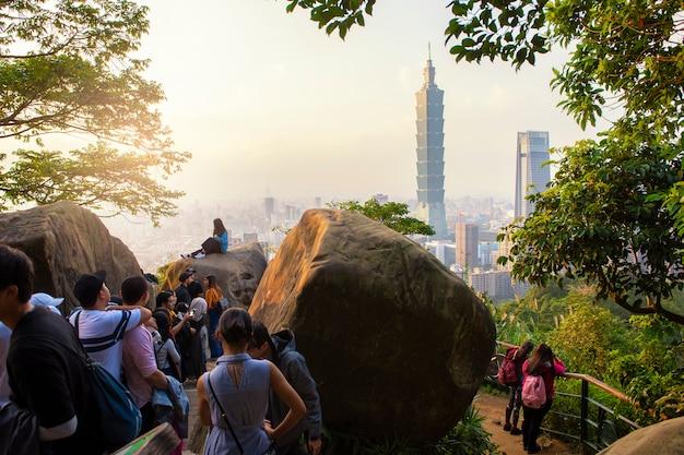 Touristes prennent des photos avec la tour 101 au coucher du soleil Photo Premium