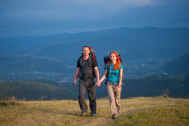 Touristes avec sacs à dos en randonnée dans les montagnes Photo Premium