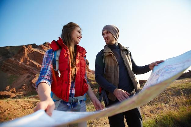 Touristes voyageant avec carte dans les montagnes Photo gratuit