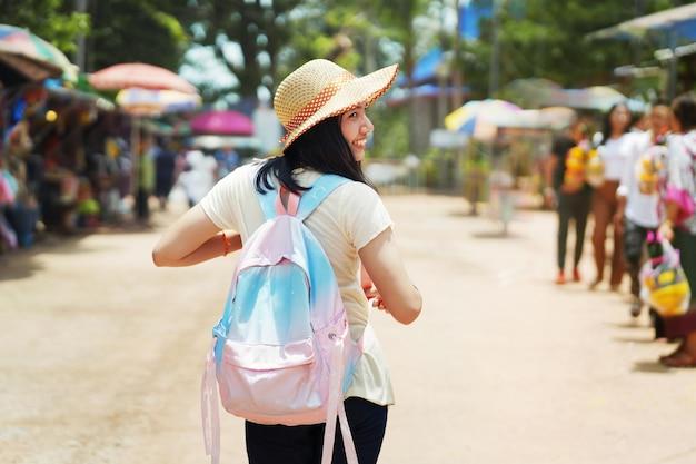 Touristique de femme asiatique avec sac à dos voyage au marché de la thaïlande Photo Premium