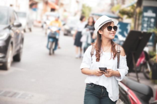 Touristique femme asiatique vérifie textos smartphone dans la rue, en utilisant l'application du téléphone mobile pour vérifier la carte en ligne. Photo Premium
