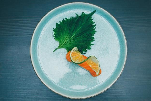 Tourné D'un Sushi De Saumon Décoré D'une Tranche De Citron Vert Et De Feuilles Vertes Sur Une Plaque Ronde En Céramique Photo gratuit