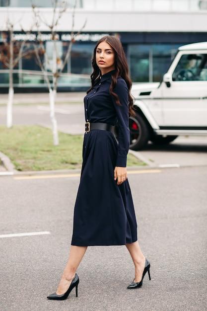 Tourné Sur Toute La Longueur De La Belle Jeune Femme élégante Vêtue D'une Robe Noire Et Marchant Dans La Rue De La Ville. Concept De Style Et De Mode Photo gratuit