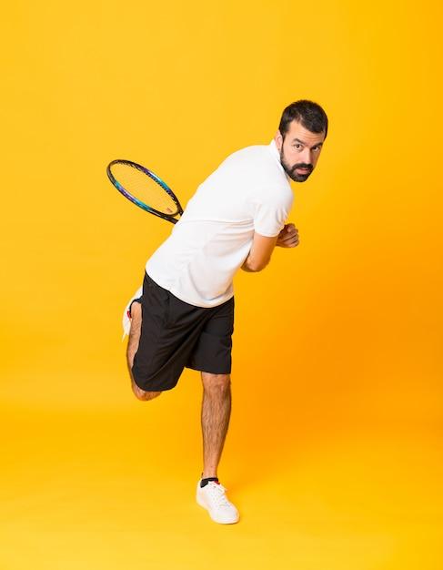 Tourné Sur Toute La Longueur De L'homme Jouant Au Tennis Sur Jaune Isolé Photo Premium