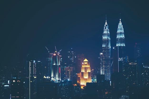 Les tours jumelles petronas (connues sous le nom de klcc) et les bâtiments environnants pendant le coucher du soleil vus du skybar Photo Premium