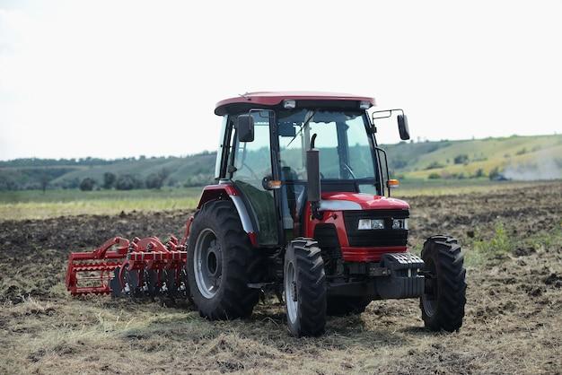Tout nouveau tracteur rouge sur le terrain fonctionne. tracteur cultivant le sol et préparant un champ pour la plantation Photo Premium