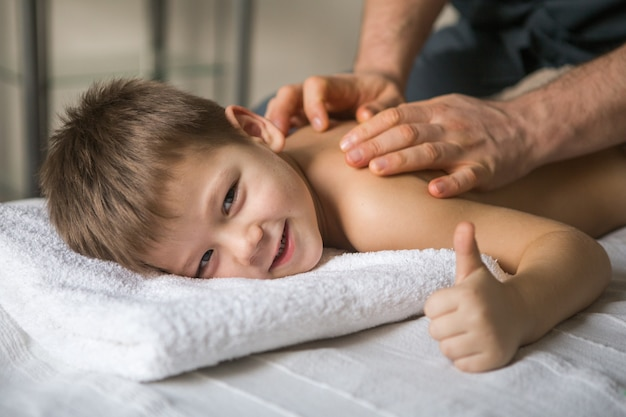 Tout-petit Garçon Se Détend D'un Massage Thérapeutique. Physiothérapeute Travaillant Avec Un Patient Dans Une Clinique à L'arrière D'un Enfant Photo Premium