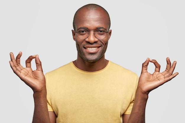 Tout Va Bien! Homme Chauve Satisfait Avec Un Sourire Positif, Des Gestes à L'intérieur, Vêtu D'un T-shirt Jaune Décontracté Photo gratuit