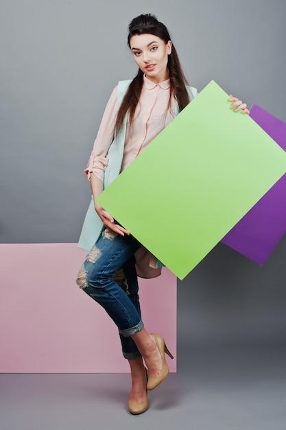 Toute la longueur de la belle fille, avec un panneau publicitaire blanc, sur fond gris et bannière rose et violette Photo Premium