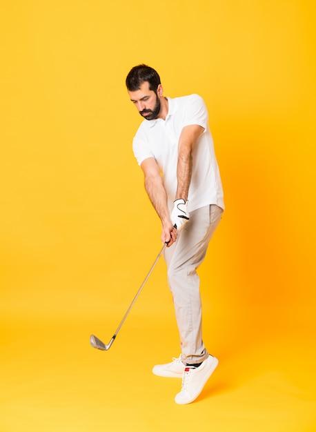 Toute la longueur d'un homme jouant au golf sur un mur jaune isolé Photo Premium