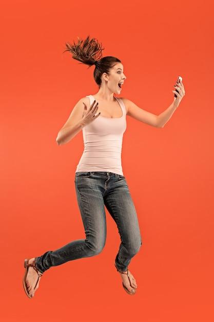 Sur Toute La Longueur De La Jolie Jeune Femme Prenant Le Téléphone En Sautant Sur Fond De Studio Rouge. Photo gratuit