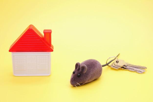 Toy mouse - un symbole de la nouvelle année, à côté d'une maison de jouets en plastique et de véritables clés de la maison. Photo Premium