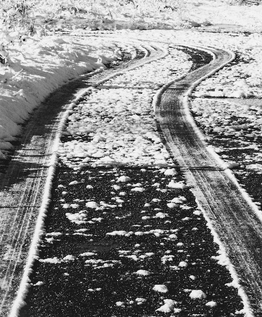 La trace des pneus sur une route enneigée, une photo monochrome en noir et blanc Photo Premium