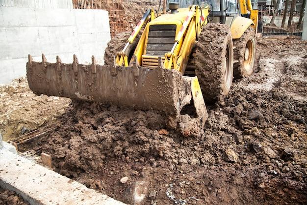 Le tracteur aligne le site pour la construction. Photo Premium