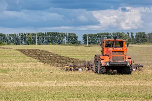 Un tracteur moderne orange laboure le champ de blé doré de la terre Photo Premium