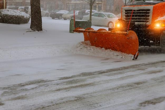 Un tracteur à neige enlève la neige pendant la neige Photo Premium