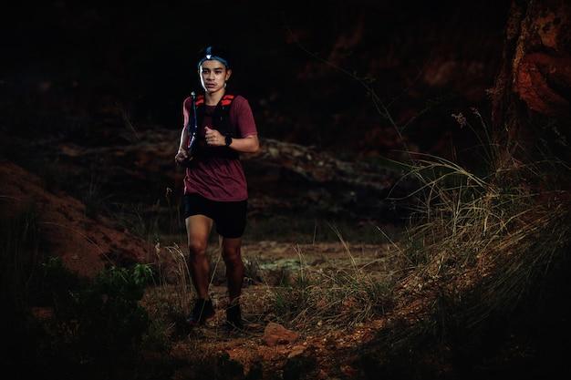 Trail coureur courir sur la route rocheuse dans la nuit Photo Premium