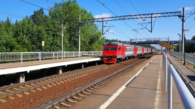 Train de banlieue arrive à la gare en été par journée ensoleillée. plate-forme ferroviaire avec train en route. Photo Premium