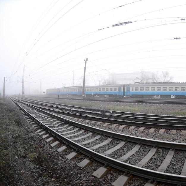 Le train de banlieue ukrainienne se précipite le long de la voie ferrée par un matin brumeux Photo Premium