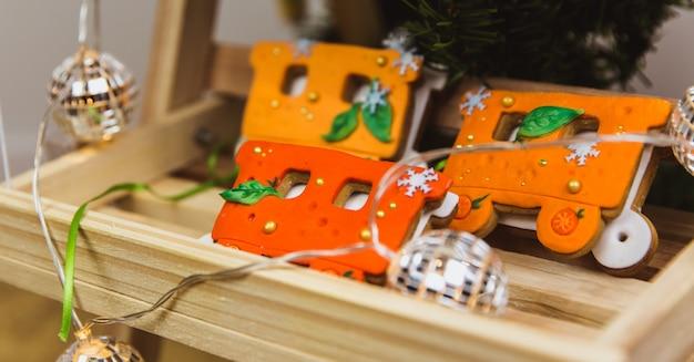 Train orange en pain d'épice de noël peint à la main sur socle en bois Photo Premium