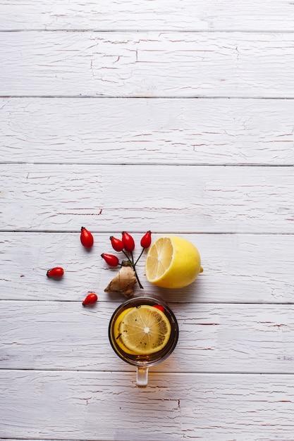 Traiter le froid. thé chaud au citron et baies se dresse sur une table en bois blanche Photo gratuit