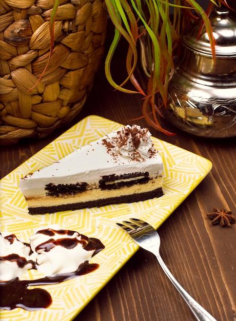 Tranche de cheesecake chocolat vanille sur plaque contre une table en bois brun rustique Photo gratuit