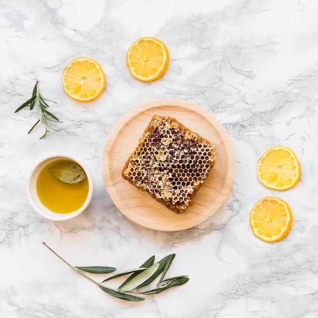 Tranche de citron, brindille avec nid d'abeille et bol d'huile sur fond de marbre blanc Photo gratuit
