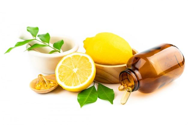 Tranche de citron frais avec des feuilles, supplément de capsule de vitamine c de naturel isolé Photo Premium