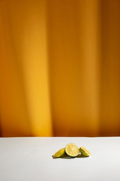 Tranche de citrons verts sur une table blanche devant un rideau jaune Photo gratuit