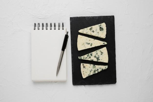 Tranche de fromage bleu disposée sur une ardoise noire avec un cahier à spirale vide et un stylo sur une surface en béton Photo gratuit