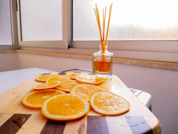 Tranche De Fruits Orange Avec Assainisseur D'air Aromatique Reed Sur Une Planche à Découper En Bois. Photo Premium