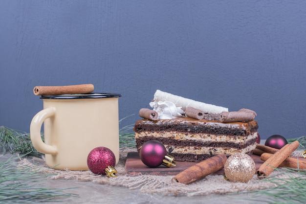 Une Tranche De Gâteau Au Chocolat Avec Une Tasse De Boisson Et Des Décorations De Noël Autour Photo gratuit