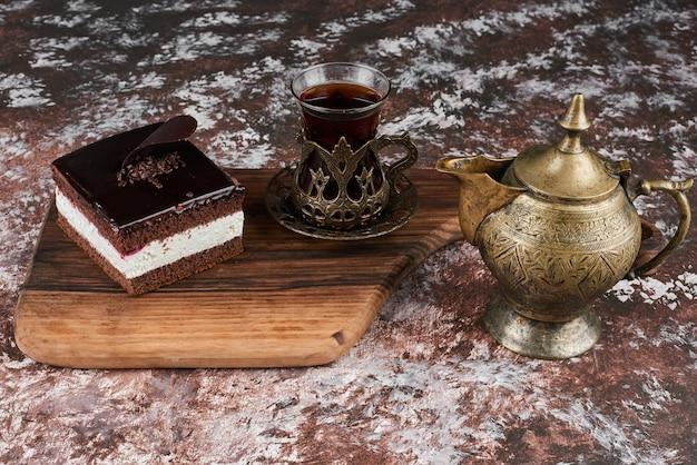 Une Tranche De Gâteau Au Fromage Au Chocolat Avec Un Verre De Thé. Photo gratuit