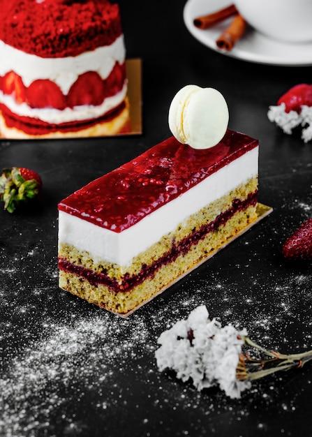 Une Tranche De Gâteau Au Fromage Aux Fraises Avec Un Macaron Blanc Sur Le Dessus. Photo gratuit