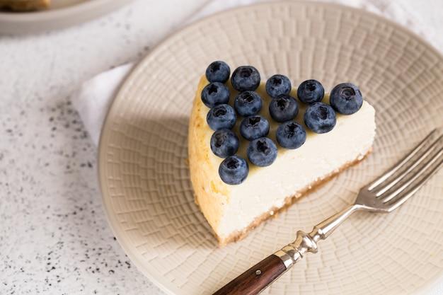 Tranche de gâteau au fromage classique de new york avec des bleuets sur une plaque blanche. vue en gros plan. boulangerie maison Photo Premium