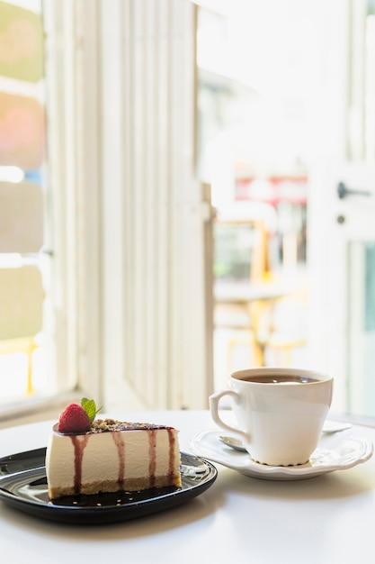 Tranche de gâteau au fromage délicieux et une tasse de thé sur la table blanche près d'une porte ouverte Photo gratuit