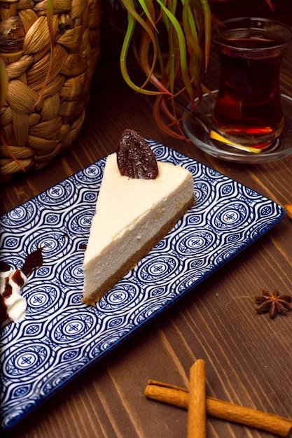 Tranche de gâteau au fromage à la vanille sur plaque contre une table en bois brun rustique Photo gratuit