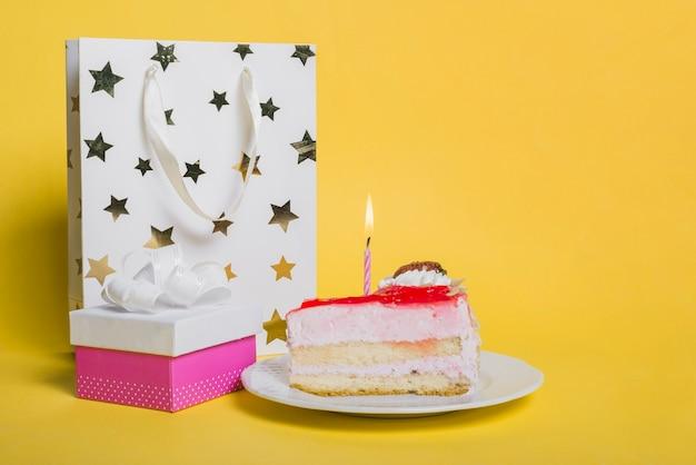 Tranche de gâteau avec une bougie allumée; sac à provisions en forme d'étoile; et coffret sur fond jaune Photo gratuit