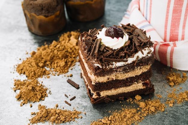 Tranche de gâteau décoratif avec chocolat en poudre sur le comptoir de la cuisine Photo gratuit