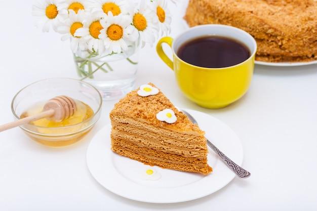 Tranche de gâteau fait maison au miel avec une tasse de thé ou de café jaune et de camomille. Photo Premium