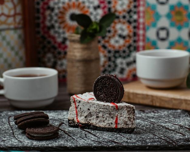 Une tranche de gâteau oreo avec un biscuit oreo sur le dessus et une tasse de thé Photo gratuit