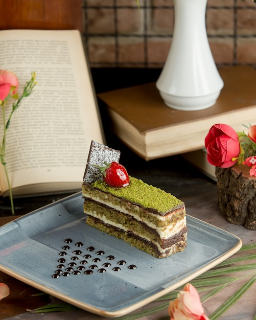 Une tranche de gâteau à la pistache émincée et aux baies de cerise. Photo gratuit